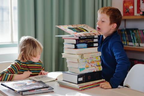 2 kinderen lezen een stapel boeken